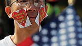 "Wearing stickers on his face, an advocate attends ""Rally for the American Dream – Equal Education Rights for All"" in Boston ahead of the start of Monday's court hearing in the lawsuit accusing Harvard University of discriminating against Asian-American student applicants."