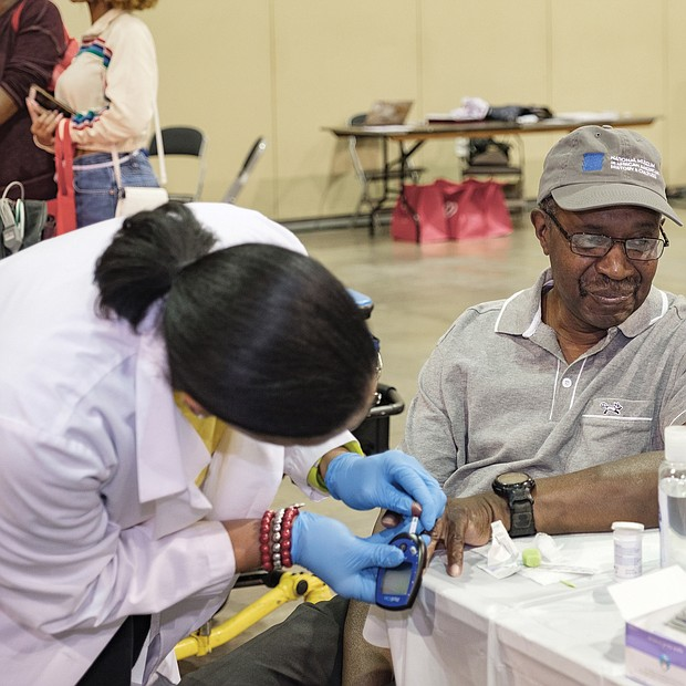 Heart talk: Ronald Bowie of Prince George has his blood sugar level checked by Kimberly Ketter, a nurse practitioner with Case Management Associates of Petersburg at the Spirit of the Heart Health Initiative at the Greater Richmond Convention Center. (Ava Reaves)