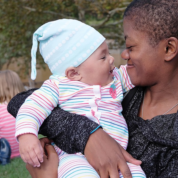 Cooing with the music: Five-month-old Coen Cheeley enjoys the music from the arms of mother Laura Cheeley at the Richmond Folk Festival last Saturday on Brown's Island. The free, three-day event on the Downtown riverfront, produced by Venture Richmond and the City of Richmond, drew musicians from across the nation and around the globe and large, appreciative crowds through the weekend. (Sandra Sellars/Richmond Free Press)