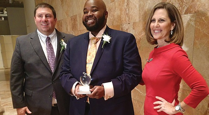 Rodney A. Robinson, the 2019 Virginia Teacher of the Year, holds the trophy he received Tuesday night at the awards ceremony at the Virginia Museum of Fine Arts. Congratulating him are Dr. James F. Lane, the state superintendent of public instruction, and Virginia First Lady Pam Northam.
