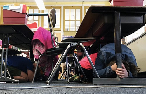 Rigler Elementary students practice what to do during an earthquake during the Great Oregon ShakeOut earthquake drill, a coordinated event ...