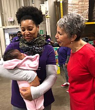 Bronwyn Mayden MSW, assistant dean at the University of Maryland School of Social Work admiring an infant.