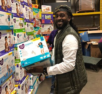 Troy Brown holding a box of diapers during the event.