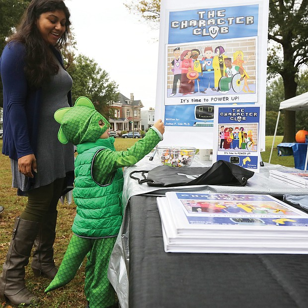 "Young book lover: Lorenzo Kenup, 3, finds his power dressed as a dragon as he and his mother, Alma Kenup, peruse book offerings at the first RVA Booklovers' Festival last Saturday in Jefferson Park. The event featured about 40 authors and poets in readings and book talks, including Joshua P. Cole, principal at Ecoff Elementary School in Chester, whose children's book, ""The Character Club,"" garnered Lorenzo's attention. Virginia First Lady Pam Northam also spoke. Proceeds from the event were to benefit local literacy organizations. (Regina H. Boone/Richmond Free Press)"