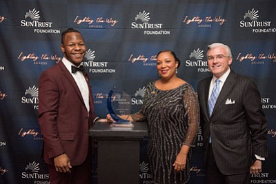 (Left to right) Gerrod A.M. Williamson, SBLC strategic initiatives coordinator;  and Tanya Terrell, SBLC executive director; receive the SunTrust Foundation's 2018 Lighting the Way Award from Dan O'Neill, SunTrust Bank Mid-Atlantic division president at a celebration in Atlanta, Georgia on October 17, 2018