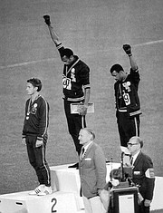 Athletes Smith, center, and Carlos give the Black Power Salute during the medal ceremony at the 1968 Summer Olympics in Mexico City. Smith finished first in the 200-meter sprint, while Peter Norman of Australia finished second and Carlos, third. All three wore human rights patches on their jackets.
