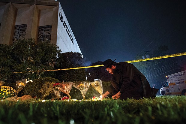 Rabbi Eli Wilansky lights a candle outside the Tree of Life Synagogue in Pittsburgh's Squirrel Hill neighborhood on Saturday night following a deadly mass shooting at the temple. Memorial flowers and candles lined the site, despite the yellow police crime scene tape.