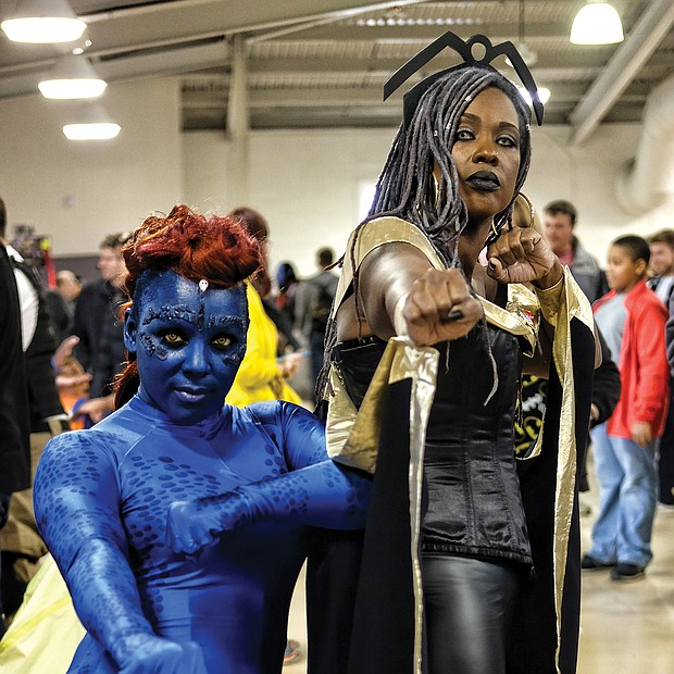"Superheroes, unite! Scores of people dressed as their favorite comic book heroes and heroines for the 2018 VA Comicon, a two-day extravaganza for comic book fans and lovers of comic book culture. Thousands flocked to the event at the Richmond Raceway last Saturday and Sunday that featured a costume contest both days. Tikki Wynn is head to toe in blue as ""Mystique"" and Honey Hall becomes ""Storm,"" all Marvel Comics characters. (Sandra Sellars/Richmond Free Press)"