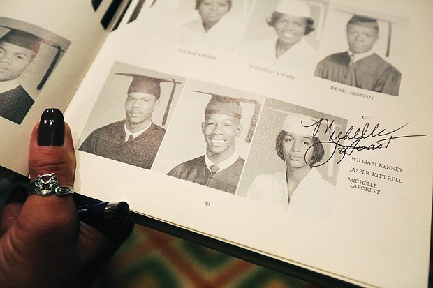 Golden memories: Members of the Armstrong High School Class of 1968 celebrate their 50th reunion at a dinner-dance Oct. 20 at Lewis Ginter Botanical Garden in Henrico. The three-day reunion brought back fond memories and memorabilia from class members. Michelle LaForest Roberts autographs her photo in the 1968 yearbook. (Regina H. Boone/Richmond Free Press)