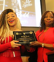 Sandy Redd (left) display her key to the village after receiving it from Mayor Shelia Chalmers-Currin at  a recent community event in Matteson