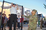 Jason Grinyshyn, 14, attempts a pull up as Sgt. Juan Rodriguez looks on during a recent Army recruitment event at Union High School in Vancouver.