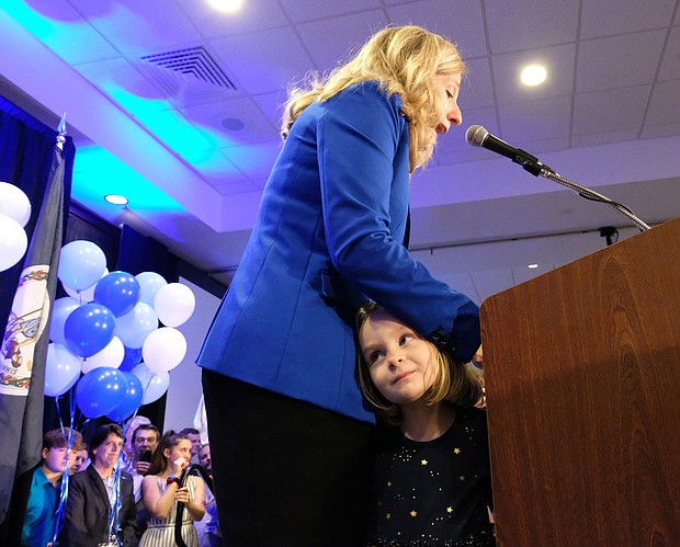 Abigail Spanberger speaks to the crowd Tuesday night as her daughter Catherine, 4, peeks out at the crowd.