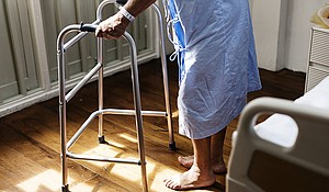 An elderly person recovers in a rehabilitation facility after sustaIning an injury from a fall.