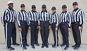 The all-female officials team, plus referee Elbert Lassiter (far right) and umpire Leonard VanHoose (far left),