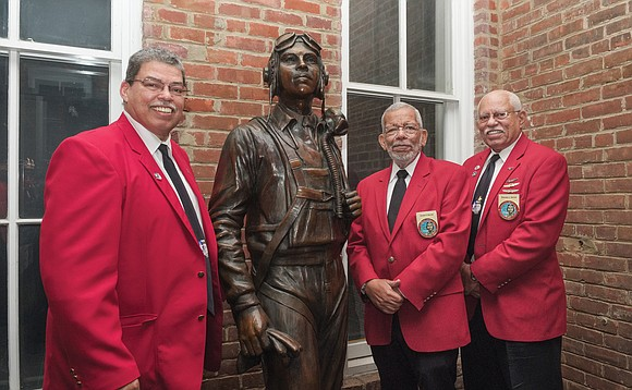 From left, brothers Richard, David and Howard Baugh stand with the life-size bronze statue of their late father, Lt. Col. ...