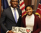 "Mayor Levar M. Stoney presents Binford Middle School student Jalia Hardy with a handmade sign after signing a proclamation declaring Nov. 12 through 16 ""Kindness Week"" in Richmond."