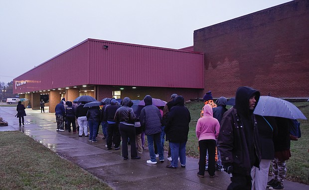 Thanksgiving comes early: Dozens of people wait in line in the rain last Thursday outside the Arthur Ashe Jr. Athletic Center in Richmond to receive boxed Thanksgiving meals. The Thanksgiving Harvest food program was sponsored by St. Paul's Baptist Church and a coalition of Richmond area organizations. (Photos by Clement Britt)