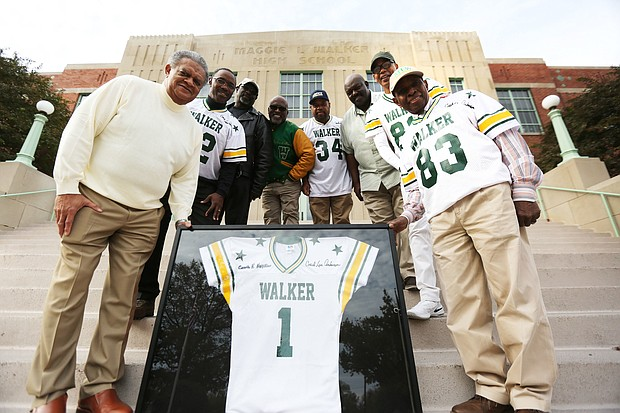 Members of the 1975 undefeated football team at Maggie L. Walker High School stand Monday on the steps of their alma mater holding a commemorative jersey they plan to present to the school. They are, from left, former Coach Richard McFee; running back Jeff Washington; flanker Richard Thomas; return specialist Richard Stuart; fullback William Washington; middle linebacker Mike Liggans; wide receiver Pierre Johnson; and former athletic director Howard Hopkins.