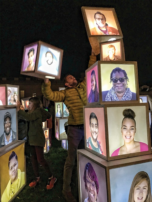 """A variety of innovative art pieces adorn the grounds of the Virginia Museum of Fine Arts' Sculpture Garden during InLight Richmond, the 11th annual light-based show of art and performances sponsored by the 1708 Gallery last weekend. Luke Hostetler participates in Kevin Orlosky's installation, """"Building Together,"""" while faces are visible. (James Haskins/Richmond Free Press)"""