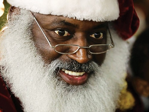 Dee Sinclair portraying Santa Claus reads a story to children in Atlanta in this archive photo from the Associated Press. A Black Santa event in Portland will be held on Sunday, Dec. 9 at the Matt Dishman Community Center.
