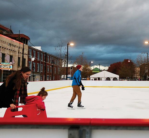 "Krista Waddell, left, and her 5-year-old daughter, Aribella, get ready to join Ian Donselaar, 18, center, on RVA On Ice's skating rink located at the 17th Street Farmers' Market near Main Street Station. Sponsored by Capital One, the rink quietly opened just before Thanksgiving at its new location. It's official opening will be Friday, Dec. 1. The rink will be open seven days a week before wrapping up the season on Monday, Jan. 21, Martin Luther King Day. ""Rock the Rink"" parties are scheduled for 8 to 10 p.m. Saturday nights in December and January. On most days, the rink and skate rental tent open at 3 p.m.; however, skating begins at 11 a.m. on Saturdays and Sundays. Details: (804) 234-3905 or https://enrichmond.org/17th-street-market/rva-on-ice. (Regina H. Boone/Richmond Free Press )"