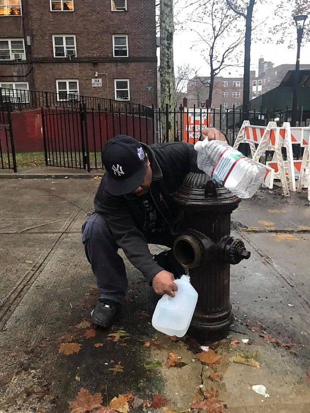 Resident at Patterson Houses gets water from a fire hydrant