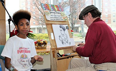"Jerry Breen, caricaturist, creates an amazing likeness of Miguel Coppedge. Miguel is the author of ""The Adventures of Fireman"" and sold his books, t-shirts and firehats at the event."