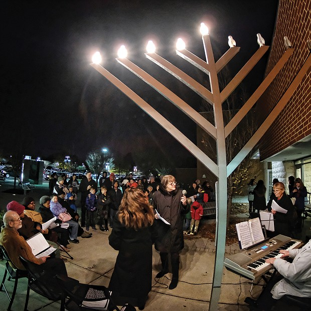 Celebrating Hanukkah: Dozens of people gather at the Weinstein Jewish Community Center in Richmond on Wednesday for the lighting of the menorah for Hanukkah. The eight-day Jewish festival of lights, which began Sunday night, commemorates the re-dedication of the Temple in Jerusalem by the Maccabees after their victory over Antiochus, who outlawed Judaism in 167 B.C. To celebrate their victory, the Jewish people tried to carry out a ritual lighting of a menorah in the temple, but found only enough oil to light it for one day. However, the oil miraculously lasted for eight days. Traditional foods and gifts are part of the religious holiday that ends Monday, Dec. 10. (Sandra Sellars/Richmond Free Press)