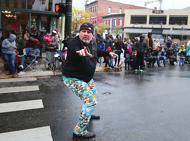"""Holiday cheer: Thousands of spectators turned out last Saturday for the 35th Annual Christmas Parade in Richmond. Dozens of huge balloon characters, floats, marching bands and Santa made their way along Broad Street from the Science Museum of Virginia east to the Richmond Coliseum in Downtown to the smiles and cheers of people of all ages. Below left, Chief Operating Officer Todd """"Parney"""" Parnell, dressed in his trademark garish pants, represents the Richmond Flying Squirrels along the parade route. (Regina H. Boone/Richmond Free Press)"""