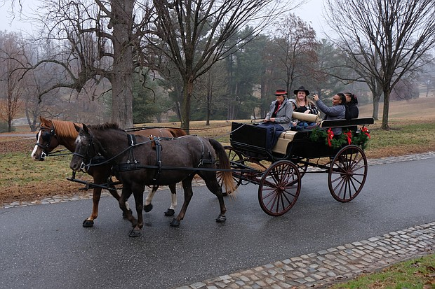 Old-fashioned Christmas: Visitors to Maymont embraced the holiday spirit last Sunday with the park's annual Old-fashioned Christmas celebration. Yolanda Smith and Brittany Powell take a selfie during a carriage ride around the grounds. The Gilded-Age mansion will be decked out for holiday tours through Jan. 6  (Sandra Sellars/Richmond Free Press)