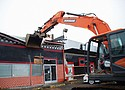 An excavator, helmed by Hacienda CEO Ernesto Fonesca, takes aim at the Sugar Shack, the former strip club in the Cully Neighborhood of northeast Portland known for harboring prostitution and other criminal activity for the past 20 years. The deconstruction began Monday after community leaders gathered to celebrate plans to replace the rundown buildings on the site with a 140-unit affordable housing development.