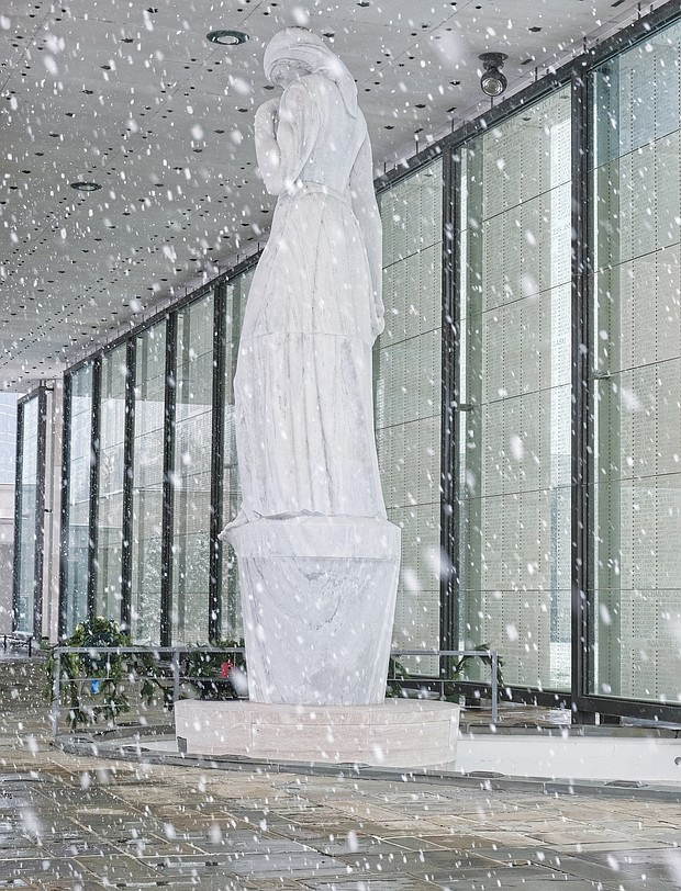 Brrrrr! The first snowfall of the season last Sunday resulted in people heading outdoors in the cold to clear snowy walkways and parking spots so that people and cars could safely maneuver. The marble statue at the Virginia War Memorial stands in contrast to the falling snowflakes. (Regina H. Boone/Richmond Free Press)
