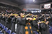 The 300 fall graduates hood one another during the ceremony and celebrated by decorating their mortar boards with flowers and other expressions.
