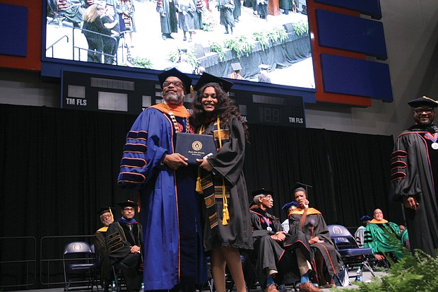 VSU President Makola M. Abdullah gives a congratulatory hug to his daughter, Sefiyetu, who received her bachelor's in mass communications during the ceremony.