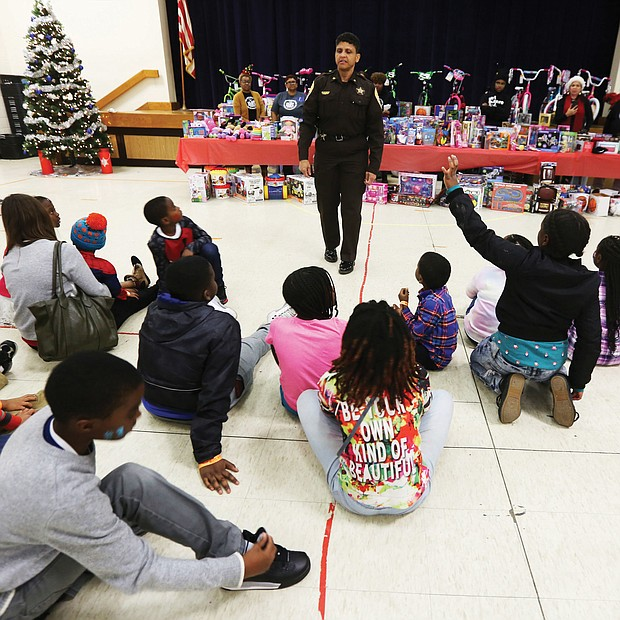 "Toys, toys, toys! Richmond Sheriff Antionette V. Irving talks with youngsters at the ""No Child Without a Toy"" event last Friday at Woodville Elementary School in the East End. The city Sheriff's Office is partnering with St. Paul's Baptist Church and AFOI, Assisting Families of Inmates, to ensure that youngsters have gifts during this holiday season. The youngsters in AFOI's ""Milk and Cookies"" mentoring program enjoyed face painting, decorating ornaments and other activities before the toys were distributed. The mentoring program is active in several Richmond elementary schools, including Woodville, Chimborazo and Swansboro. (Regina H. Boone/Richmond Free Press)"