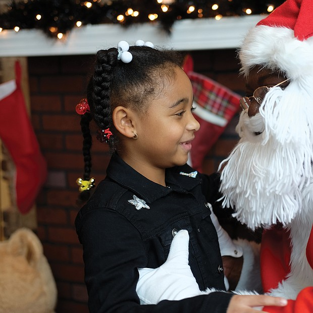 Leave it to Santa: Skye Cook, 6, tells all her Christmas wishes to Soul Santa during a recent visit to the Black History Museum & Cultural Center of Virginia in Jackson Ward. Soul Santa is always a big hit at the museum on December weekends leading up to the holiday. In just a few days, the youngster will see if Santa truly delivered. (Sandra Sellars/Richmond Free Press)