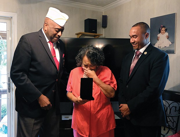 Towanda C. Lee of Mechanicsville cries as she and her brother, Damon R. Charity, right, receive the Congressional Gold Medal on behalf of their father, the late Sgt. Herman Russell Charity Sr., who was one of the nation's Montford Point Marines. Retired Master Sgt. Forest E. Spencer Jr., left, presented the award in October.