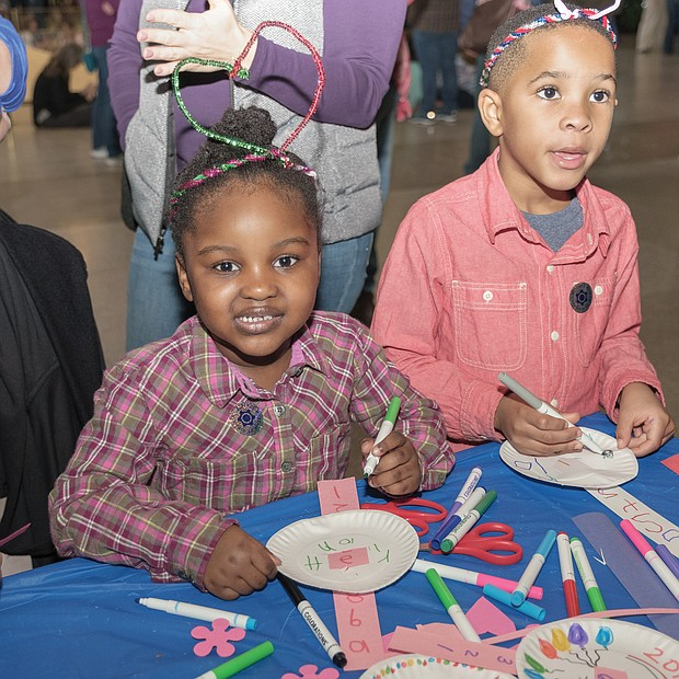 "Ringing in the new year: Confetti rains down on 2,500 youngsters and their families gathered at the Science Museum of Virginia to ring in 2019 early — at noon on Monday. Youngsters, including Aleyah Michael, 4, left, and Brycen Woodson, 5, made wearable decorations for the ""Noon Year's Eve"" celebration, which featured a giant party ball, music, countdown, noisemakers and a parade. Youngsters also could sign a huge banner with their resolutions for 2019. (Photo by Ava Reaves)"