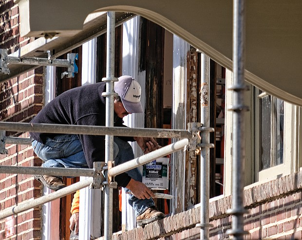 A worker paints windows last Saturday on the former Fulton Elementary School property that is being renovated into 33 apartments in the city's East End. (Sandra Sellars/Richmond Free Press)