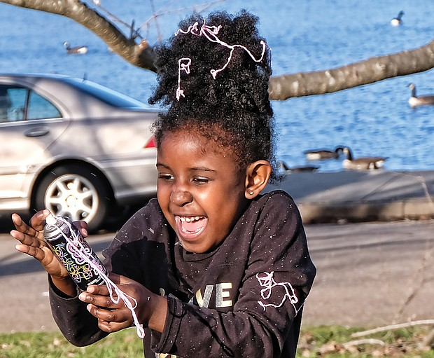 Warming up to winter: Chelsea Garba, 5, gets carried away with a spray can of Goofy String while playing with her dad, Makka Garba, by Fountain Lake in Byrd Park last Saturday, when the day was sunny and temperatures hovered near 60 degrees. What a change this weekend will bring, when high temperatures will be in the 30s, with snow forecast for Sunday. (Sandra Sellars/Richmond Free Press)