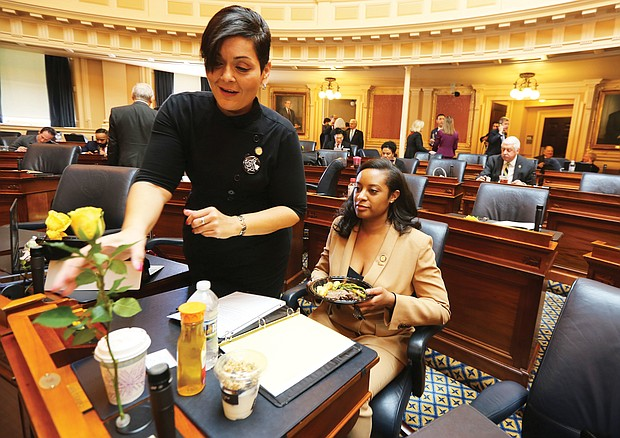 New year, new session: Delegate Hala S. Ayala of Prince William County adjusts a yellow rose — representing support for the ERA — on the desk of a Prince William colleague, Delegate Jennifer D. Carroll Foy. (Regina H. Boone/Richmond Free Press)