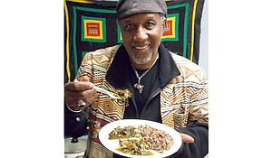 Professor Freedom enjoying a Jubilee Day freedom meal of collard greens grown in his Sankofa Garden, along with blacked-eyed peas and brown rice. He used smoked turkey rather than pork in both dishes for a healthier alternative.