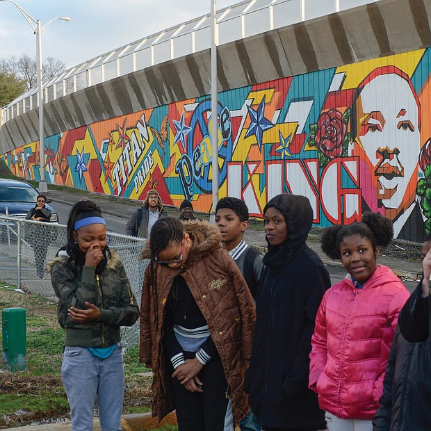 Happy 90th Birthday, Dr. King! Richmond Schools Superintendent Jason Kamras, right, speaks at the dedication Tuesday of a new mural honoring Dr. Martin Luther King Jr. that is located on the entryway to the Martin Luther King Jr. Bridge and adjacent to the Martin Luther King Jr. Pre-School Learning Center at 900 Mosby St. in the East End. The dedication was held on what would have been Dr. King's 90th birthday. It is the second King mural on the site done by U.N.I.T.Y. Street Project; the first was completed in July. Muralists Sir James Thornhill and Hamilton Glass joined in the dedication ceremony, along with students from Martin Luther King Jr. Middle School who worked on the project. (Clement Britt)