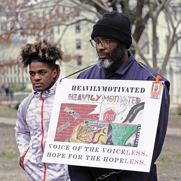 Rallying for prison reform: Hampton residents Wyheem Vessels, left, and Thurston White join more than 200 people who turned out to protest against solitary confinement and other prisoner-related issues at the 2nd Annual Prison Reform Rally at Capitol Square last Saturday. A coalition of advocates, former prisoners and relatives held the event to promote legislation to abolish solitary confinement, cut lengthy sentences and restore parole or the system of early release for model prisoners that was abolished in 1995.  (Sandra Sellars/Richmond Free Press)