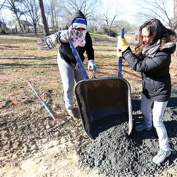 """Rachel Motley, left, and Erin Almquist of Richmond pitch in to care for a biking and walking trail at Bellemeade Park in South Side on Monday as part of the City of Richmond's """"In Pursuit of the Dream"""" events."""