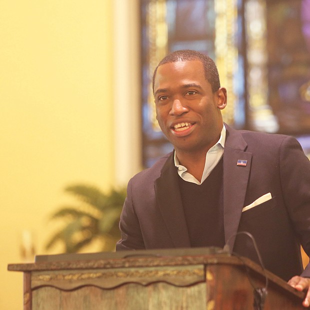 A participant holds a program as Mayor Levar M. Stoney speaks at St. Elizabeth's Catholic Church to launch the city's King Day volunteer activities.