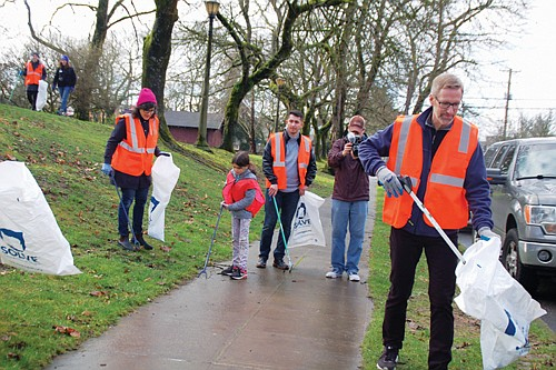 Mayor Ted Wheeler (right) helps clean up around Irving Park on Northeast Fremont Street on Monday, one of hundreds of ...