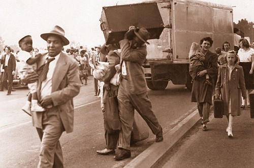 People carry what they can during an evacuation of Vanport as Columbia River floodwaters pour into the town just north of Portland from a broken railroad levy on May 30, 1948. Soon the entire town would be washed away. The Vanport Mosaic project is sharing oral histories from of life in Portland during the time and over the course of Portland's African –American history.