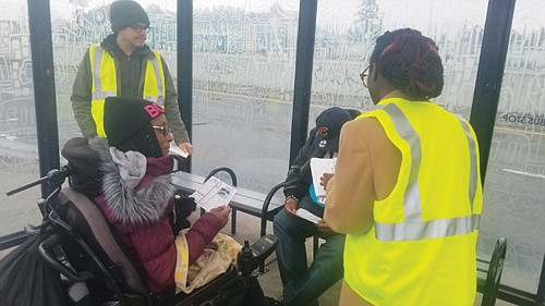 Yellow-vested Tristan Isaac (left) and Shanice Clarke (right) are leaders of the transit equity advocacy group Bus Riders Unite. The photo (above) shows them at a transit stop speaking to community members about how to obtain reduced-price fares for low income people.