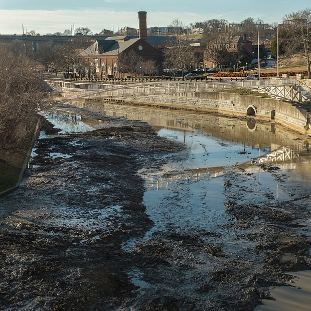 A front-end loader scoops out the sediment choking the Haxall Canal in Downtown, whose waters once powered an electric plant. The work to dredge the canal from Brown's Island to 12th Street began Jan. 15 and is expected to take four months, according to the city Department of Public Utilities, which is managing the job. Cost: $1.5 million. The water in the canal also is being drained, above, the department said, adding it is working with the state to save the fish that will be affected.  The canal, which receives its water and sediment from the James River, was last cleaned in 2008. The work is needed every 10 to 15 years, according to DPU officials, to protect the equipment that controls the level of water in the canal and to improve the flow.  The department briefly drained the canal last summer to conduct a survey in preparation for this work. The canal also is drained periodically to remove sediment that accumulates at the head gates, DPU officials stated. (Ava Reaves)